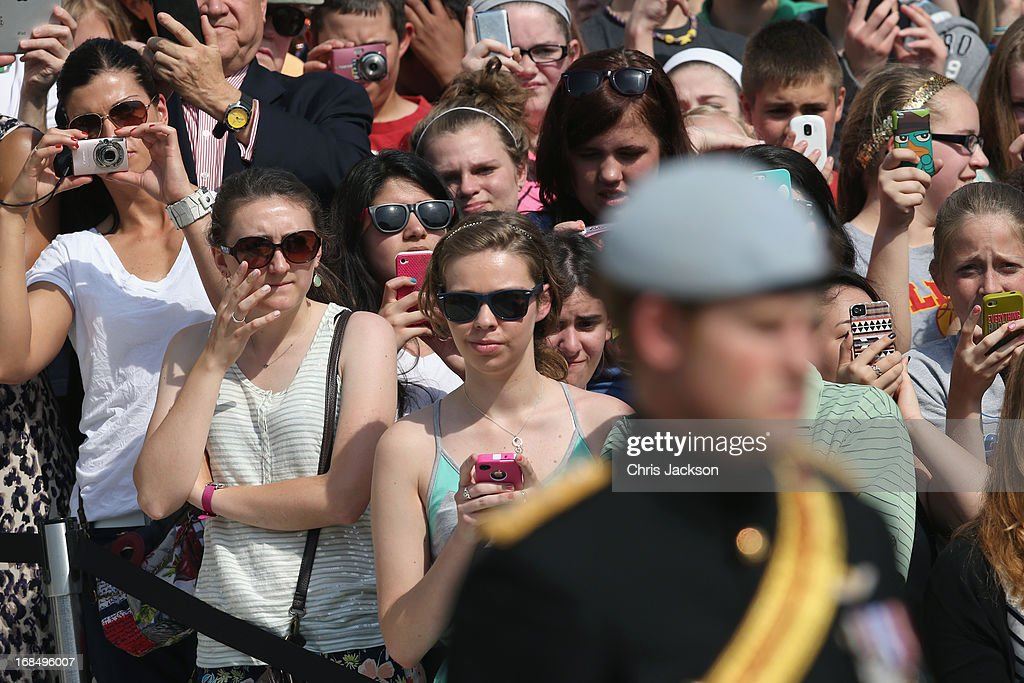 Women take pictures with their smartphones as HRH Prince Harry wearing his No. 1 ceremonial uniform of The Blues and Royals pays his respects to the victims of the Afghanistan conflict and the tomb of the unknown soldier during the second day of his visit to the United States at Arlington National Cemetery on May 10, 2013 in Arlington, Virginia. HRH will be undertaking engagements on behalf of charities with which the Prince is closely associated on behalf also of HM Government, with a central theme of supporting injured service personnel from the UK and US forces.