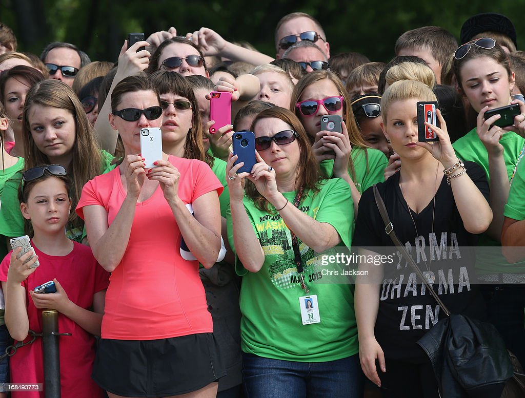 Women take pictures with their smartphones as they wait for HRH Prince Harry to arrive during the second day of his visit to the United States at Arlington National Cemetery on May 10, 2013 in Arlington, Virginia. HRH will be undertaking engagements on behalf of charities with which the Prince is closely associated on behalf also of HM Government, with a central theme of supporting injured service personnel from the UK and US forces.