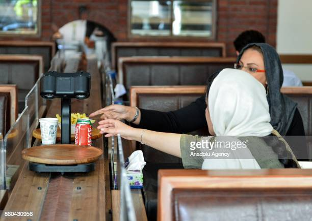Women take their food served by robot waiter which moves on rail system placed between tables at the first robotic restaurant 'RoboChef' in Tehran...
