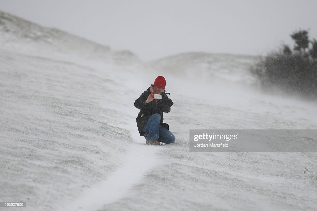 A women takes pictures of the snow whilst walking her dog at Devils Dyke on the South Downs on March 11, 2013 in Brighton, United Kingdom. Snowfall is affecting Southern parts of the UK with yellow severe weather warnings issued for London and South-East England.