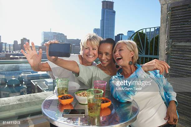 Women taking cell phone picture together at rooftop bar