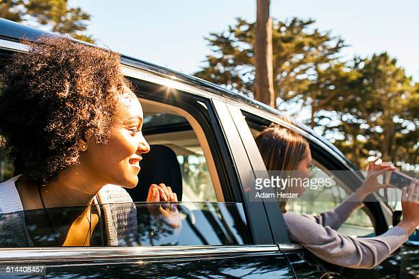 Women taking cell phone picture together in car