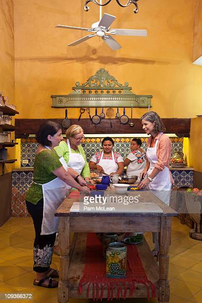 Women taking cooking lessons in a Mexico kitchen.