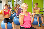 Women Taking Part In Gym Fitness Class Looking Ahead