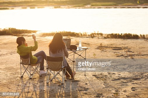 Women taking photo and surfing on net outdoors.