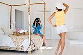 Women taking picture in bedroom