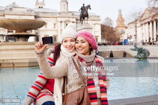 Women taking self portrait in trafalgar square. : ストックフォト