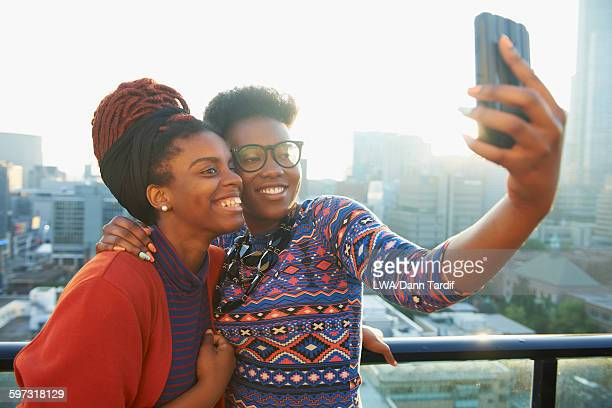 Women taking selfie on city rooftop