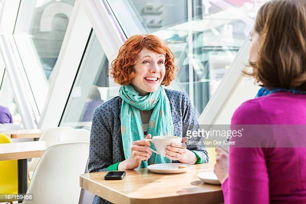 Women talking drinking coffee in cafe