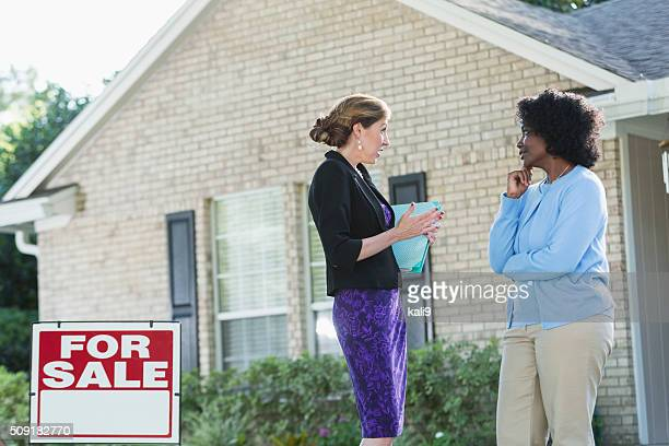 Women talking in front of house for sale