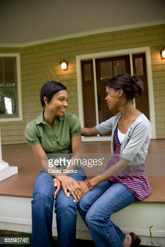 Women talking on front porch : Stock Photo