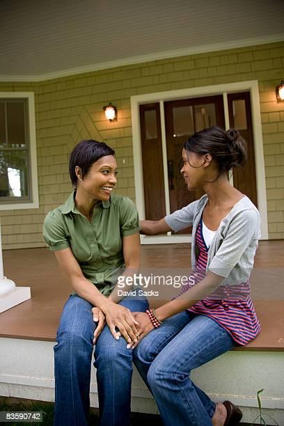 Mujeres hablando en porche de entrada