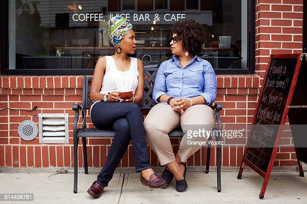 Women talking outside coffee shop on city street
