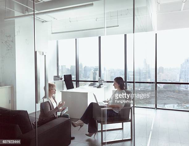 Women talking together in business office