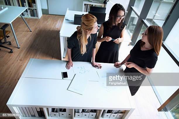 Women talking together in design planning office