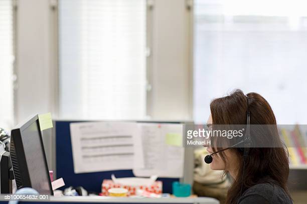 Women talking with headset in office, smiling