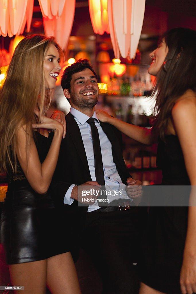 Women talking with man in bar : Stock Photo