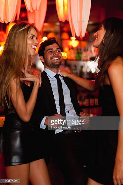 Women talking with man in bar