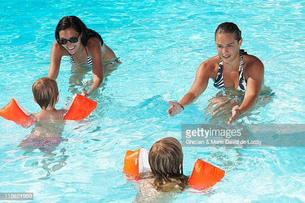 Women teaching to kids how to swim