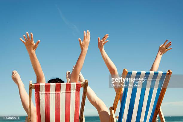 Women throwing arms in air sitting in deckchairs.