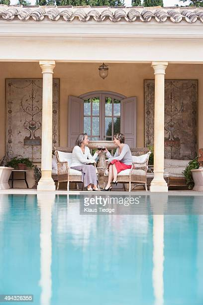 Women toasting each other by swimming pool