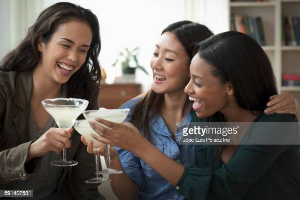 Women toasting with cocktails in living room