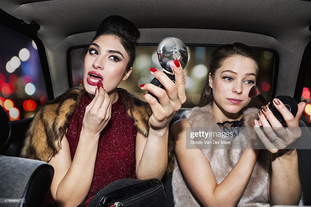 Women touching up make up in car at night time.