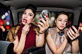 Women touching up make up in car at night time.