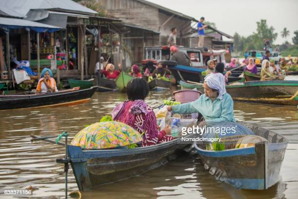 Women trading from boats at the floating market