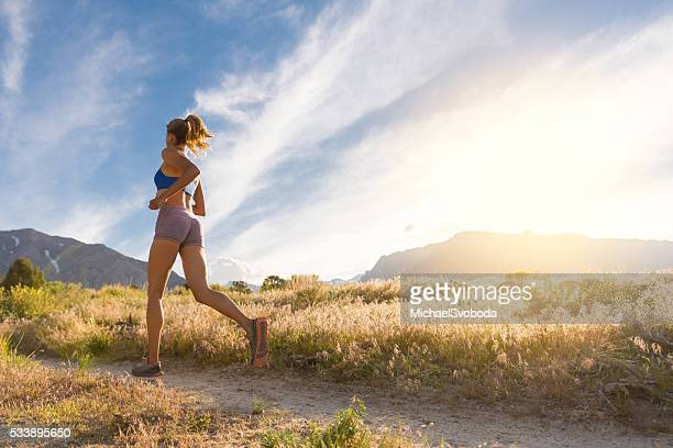 Women Trail Runner Running At Sunset In The Mountains