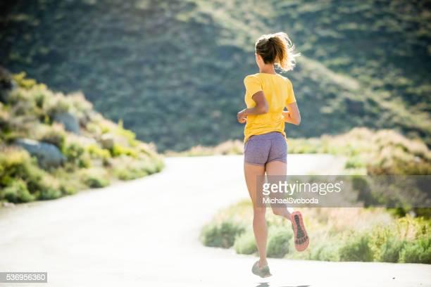 Women Trail Runner Running In The Mountains
