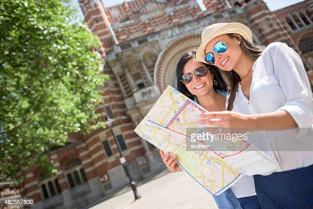 Women traveling for the summer and holding a map