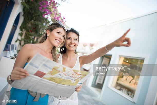 Women traveling pointing their destination and holding a map