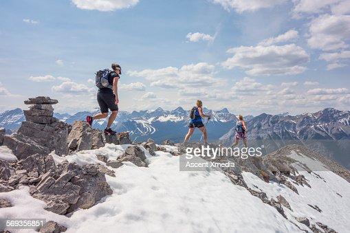Women traverse snowy mountain summit ridge