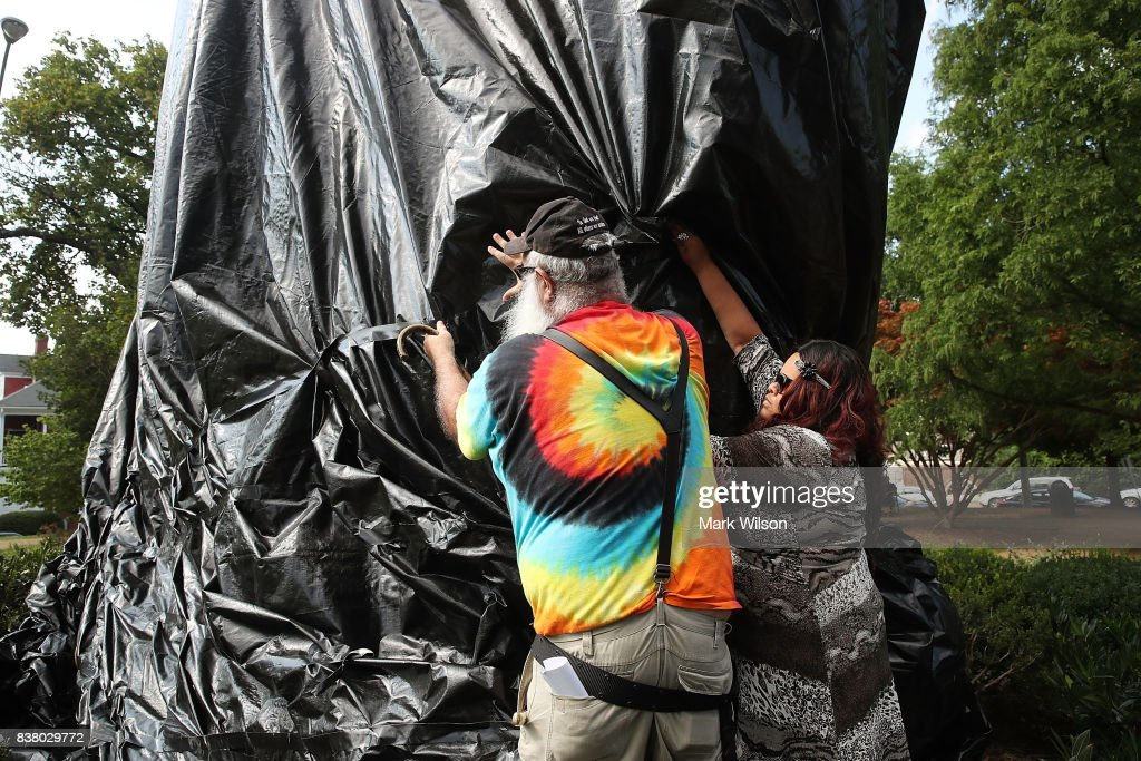 A women tries to stop John Miska from cutting off the black tarp that was put over the statue of Confederate Gen. Robert E. Lee that stands in the center of Emancipation Park (formerly Lee Park), on August 23, 2017 in Charlottesville, Virginia. Earlier this week the Charlottesville city council voted unanimously to cover Confederate statues.
