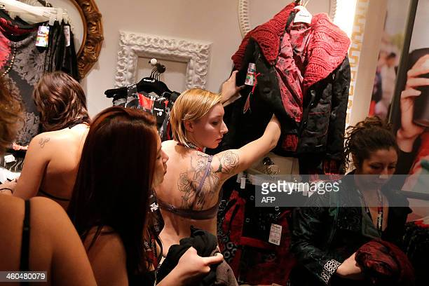 Women try clothes in a Desigual fashion store as part of the 'Semi naked party'' offer at 'Le Gru Store' in Grugliasco near Turin on January 4 2014...