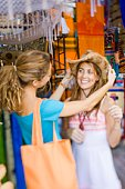 Women trying on hat at souvenir shop