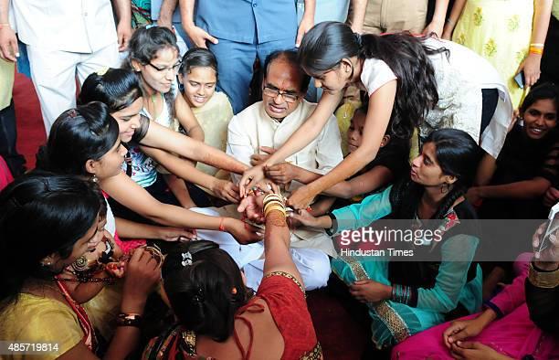 Women tying 'Rakhi' to the Madhya Pradesh Chief Minister Shivraj Singh Chouhan during a special Raksha Bandhan programme organised at CM house on...