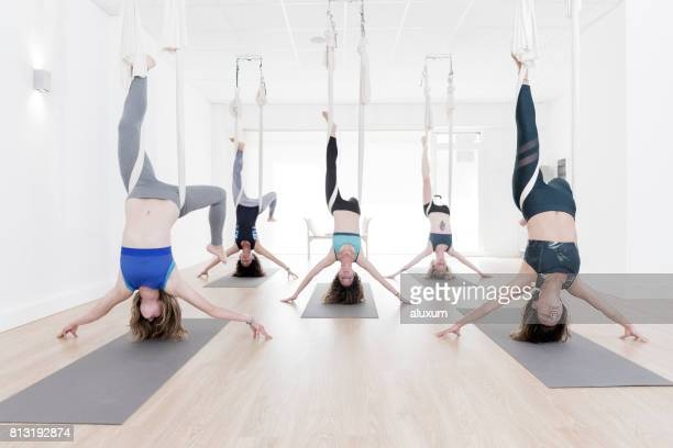 Women upside down during aerial yoga class