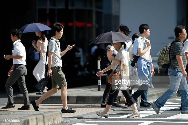 Women use umbrellas to shelter from the sun as they cross a road in Tokyo Japan on Monday July 13 2015 The Japan Meteorological Agency reported that...