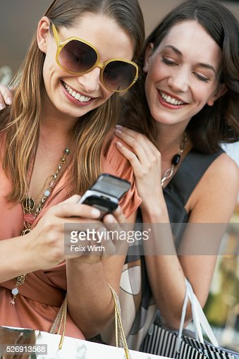 Women using cell phone while shopping : Stock Photo
