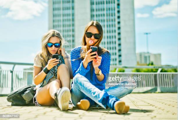 Women using cell phones on city street