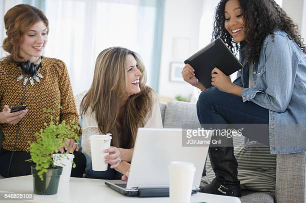 Women using digital tablet and laptop in living room