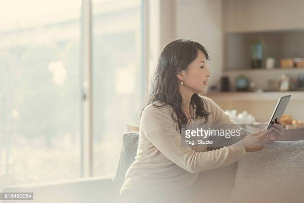 Women using digital tablet and sitting on the sofa