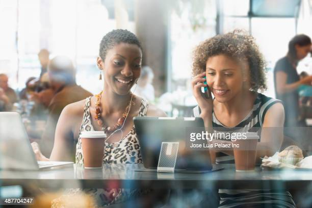 Women using digital tablet in cafe