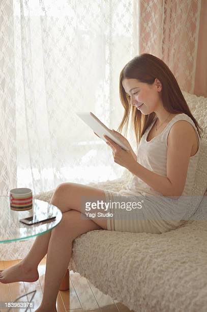 Women using digital tablet on the sofa.