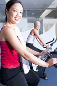 Women using exercise machines in gym