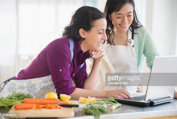 Women using laptop and cooking together