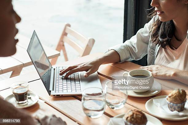 Women using laptop computer in coffee shop