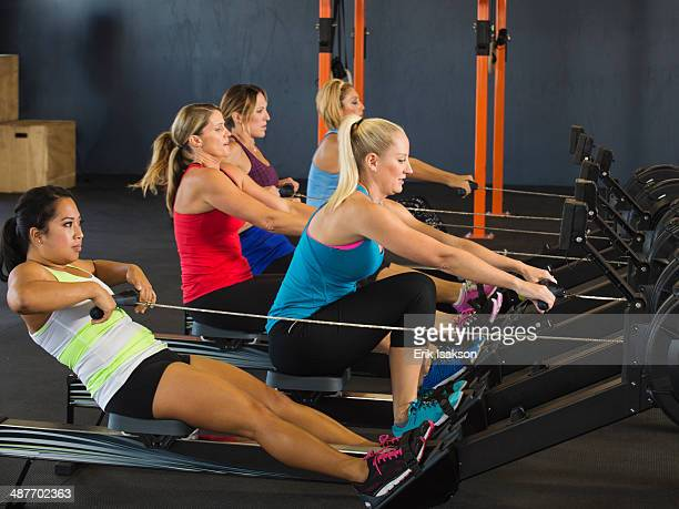 Women using rowing machines in gym